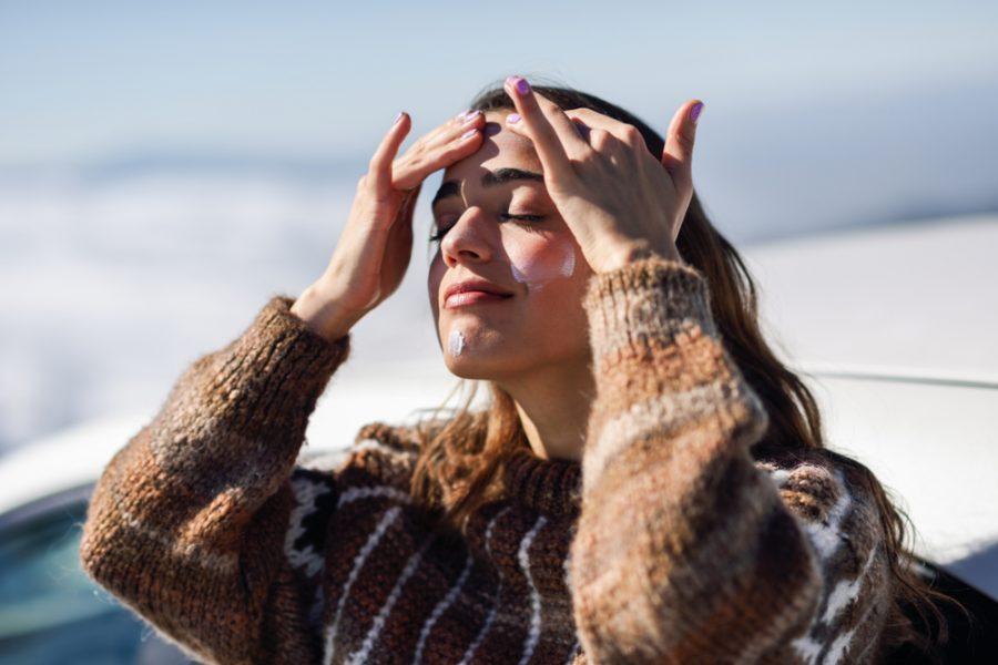 Mulher jovem utilizando protetor solar no rosto durante inverno
