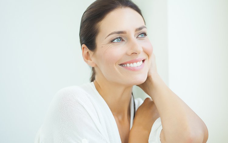 Retinol: Mulher vestida de branco olhando através de uma janela