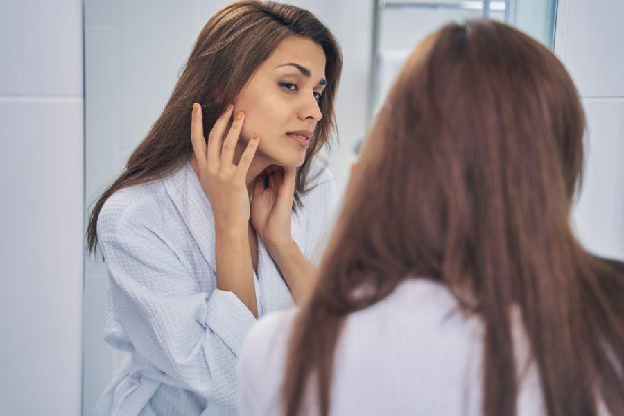 Mulher jovem observando o rosto no espelho após realizar peeling diário