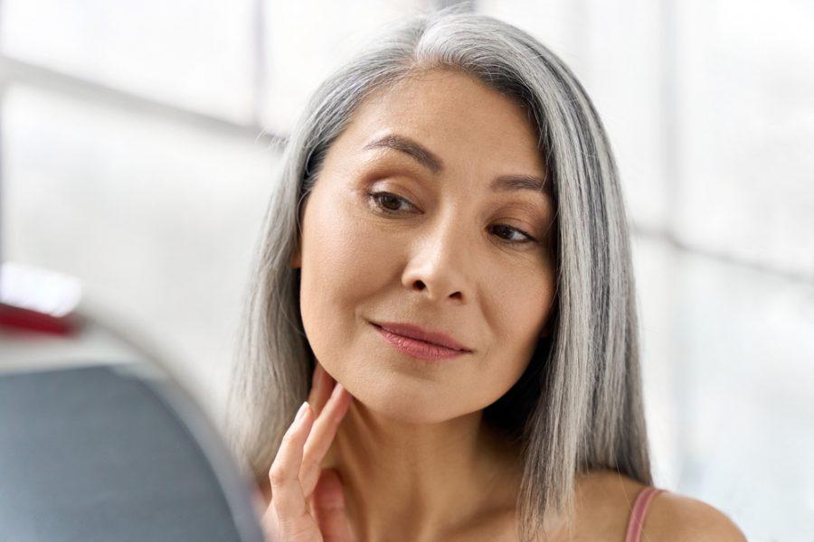 Mulher asiática de meia idade observando o rosto no espelho após realizar peeling