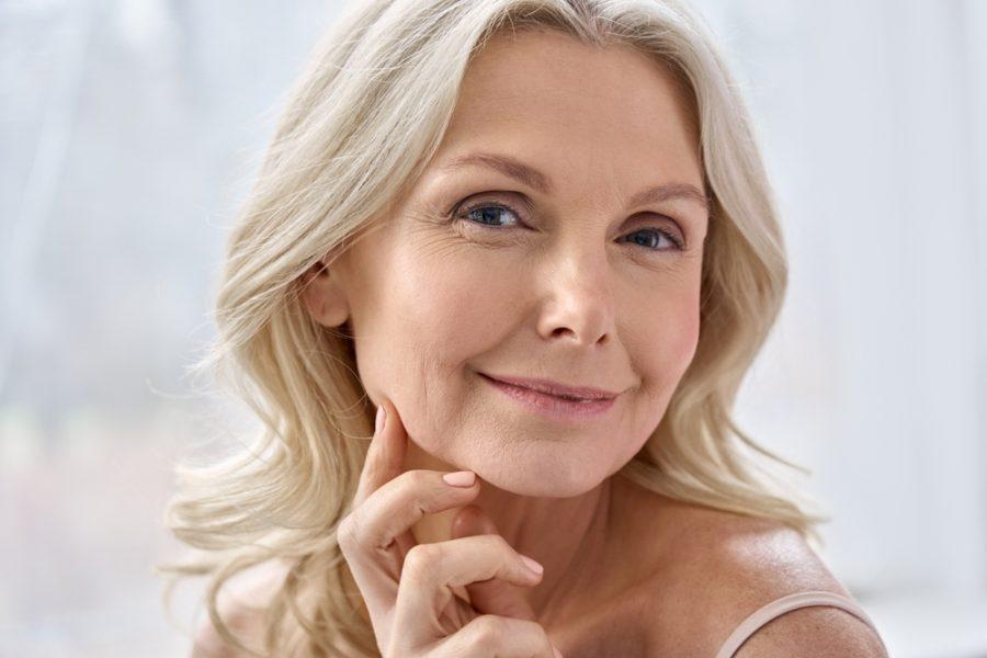 Mulher de meia idade ilustra conteúdo sobre peeling para reduzir manchas e com efeito anti-idade