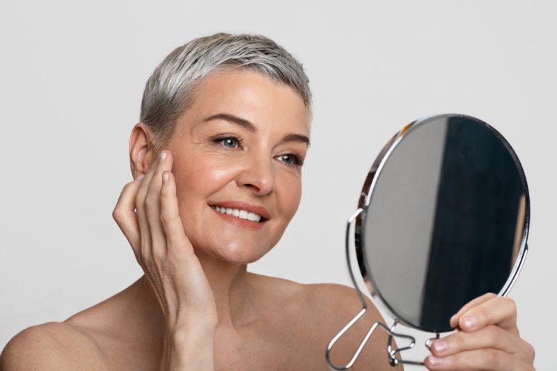 Mulher de meia idade olhando-se no espelho