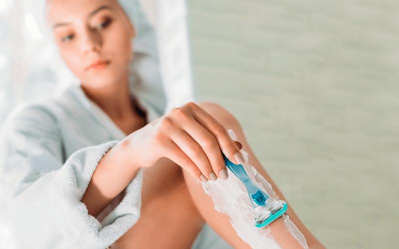 Foliculite: mulher no banho usando lâmina para depilação das pernas