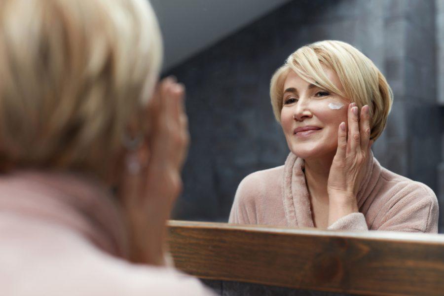 Mulher de meia idade apreciando o rosto em frente a um espelho ao realizar skincare