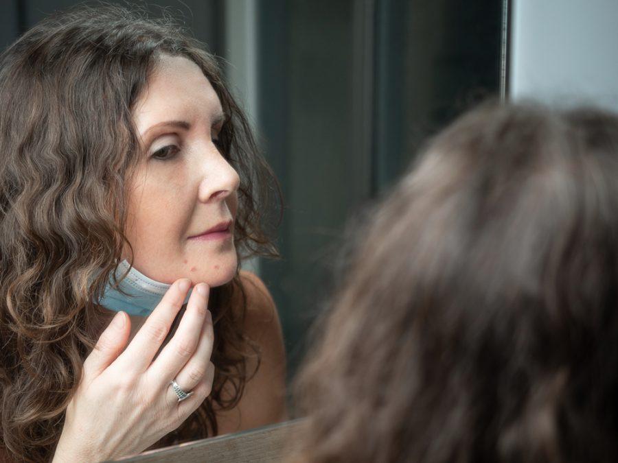 Mulher de meia idade conferindo espinhas no espelho
