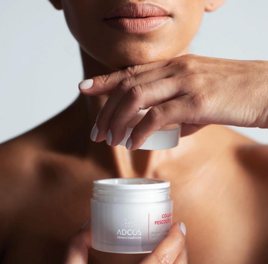 Mulher jovem segurando em mãos o creme Collagen Pescoço e Colo, da ADCOS